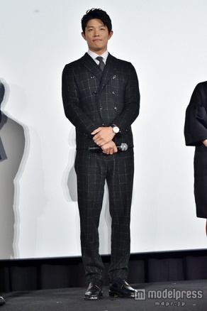ステージ上に立っている鈴木亮平さんの全身像