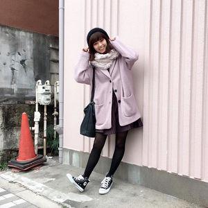 紫色のコートを着て足を伸ばしている西野七瀬