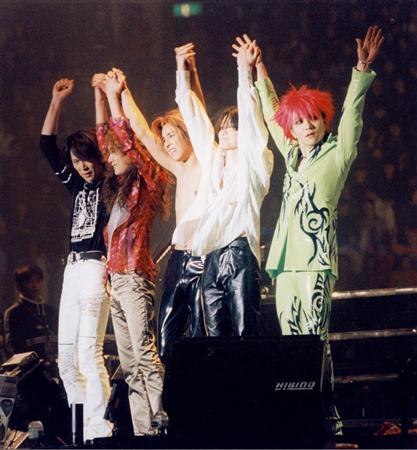 ステージでメンバーが手をつないであげているX JAPANの画像